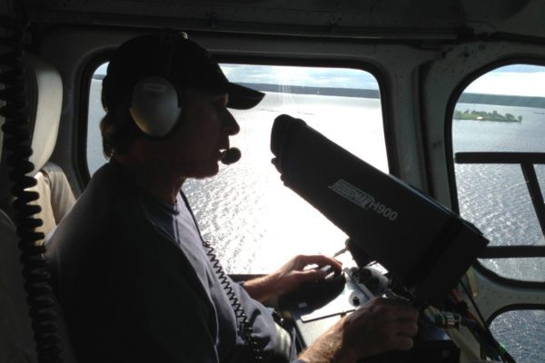 Man operating camera from inside helicopter