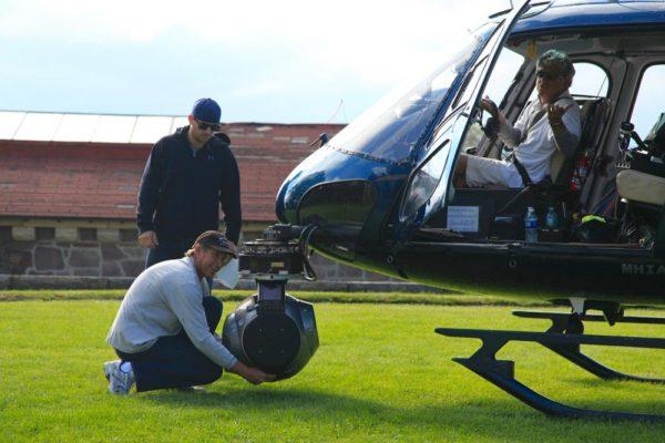 Men adjusting camera mounted on helicopter